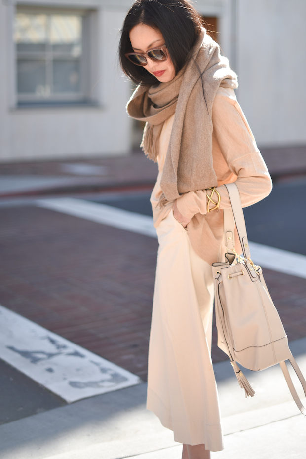 Ann Taylor is wearing a tan bucket bag from Land's End