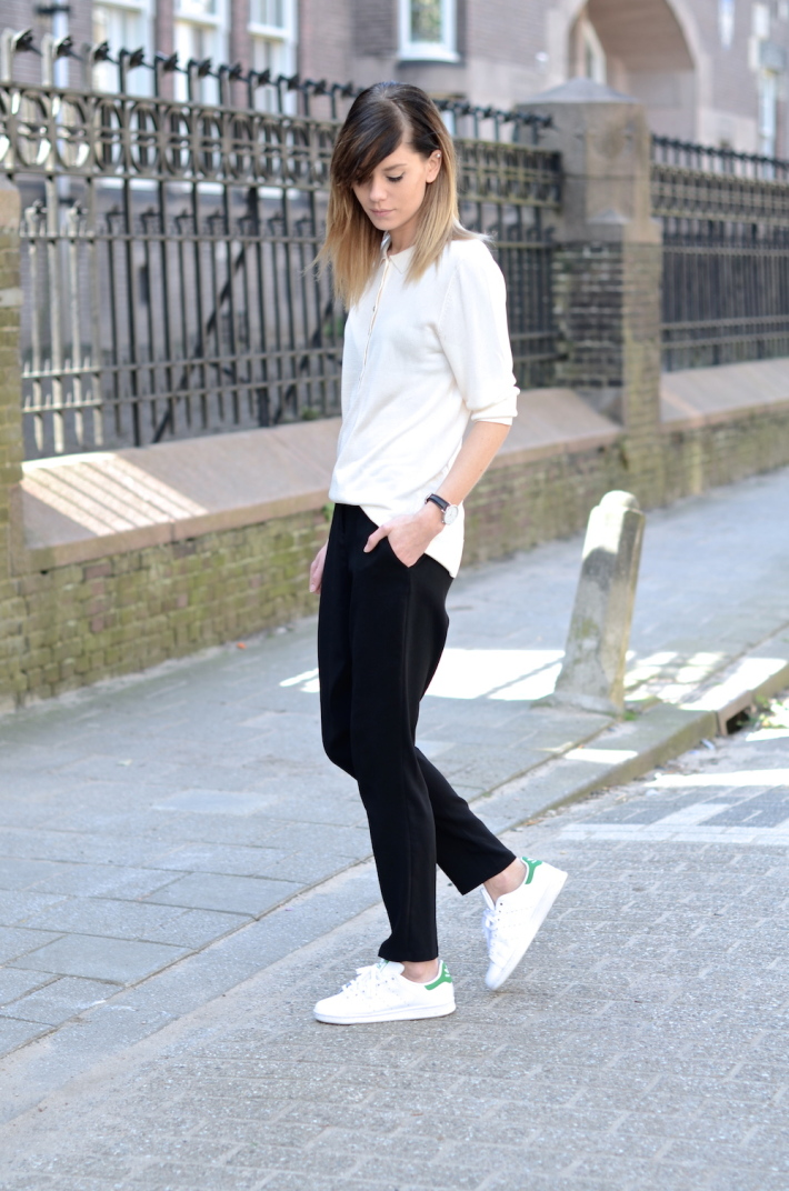 Black And White Outfits For Spring: Lovely by Lucy is wearing a collared Weekday white shirt with black Asos trousers and Adidas sneakers