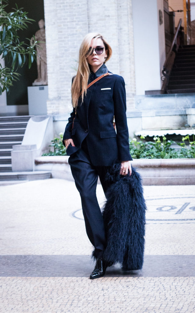 Evangelie Smyrniotaki is wearing a black blazer, pinstrioed trousers, faux fur jacket and shoes from By Malene Birger and the bag is from Celine