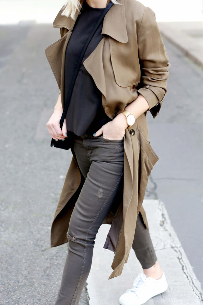 Jessie Bush wears traditional military khaki in this sophisticated outfit consisting of skinny jeans, a black tee, and a classic trench coat. We love the military aspect of this every day look. Trench: Dress Up, Tee/Jeans: Nobody, Bag: Saint Laurent.