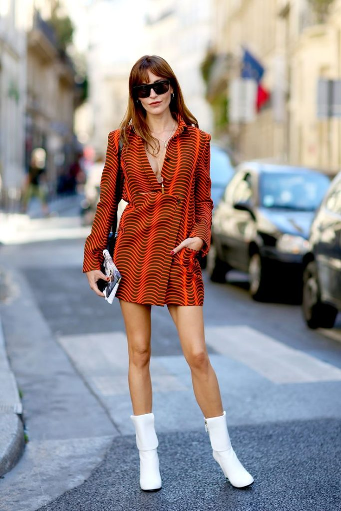 The 70's Trend Is Here To Stay: Ece is wearing a long sleeve mini dress and white boots