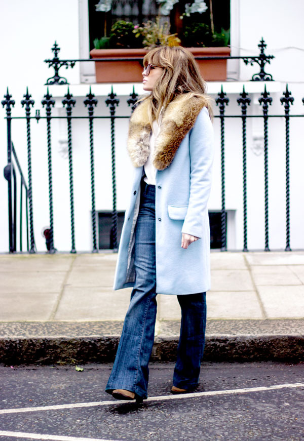 70s Style Inspiration: Isabel Sellés is wearing a pale blue coat from Fashion Union, vintage furry stole, flare jeans from Zara and the boots and white shirt are from Zara