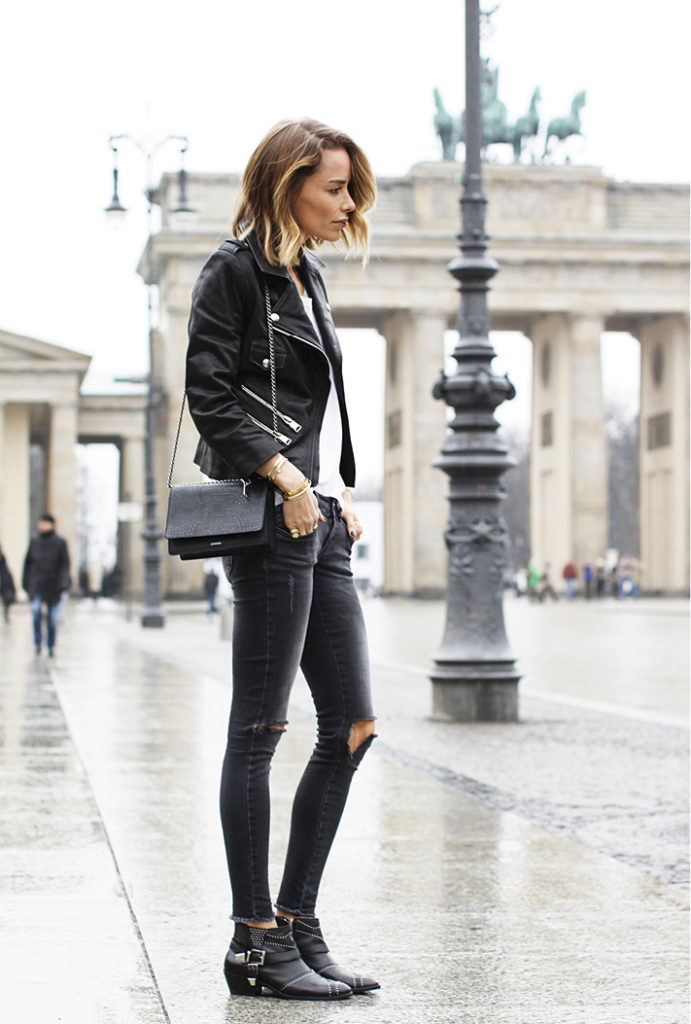 Anine Bing is wearing a mini coco bag, black ripped jeans, studded boots with buckle and striped T-shirt all from Anine Bing