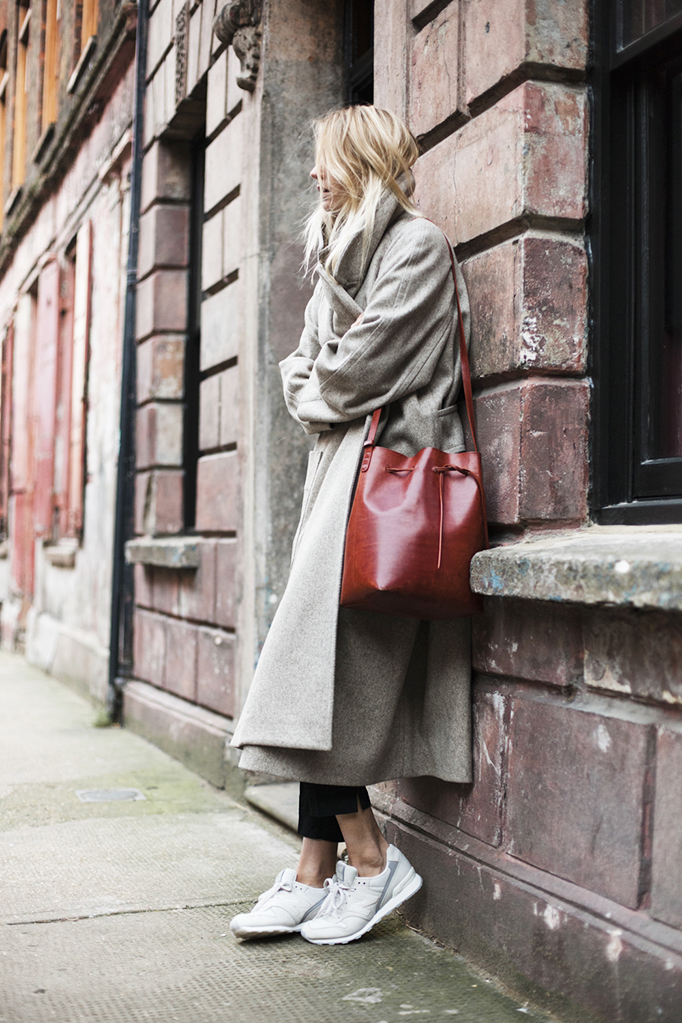 Camille Charriere is wearing a is wearing a grey long coat coat from Christophe Lemaire cigarette trousers from Etro, sneakers from New Balance and the red bag is from Mansur Gavriel