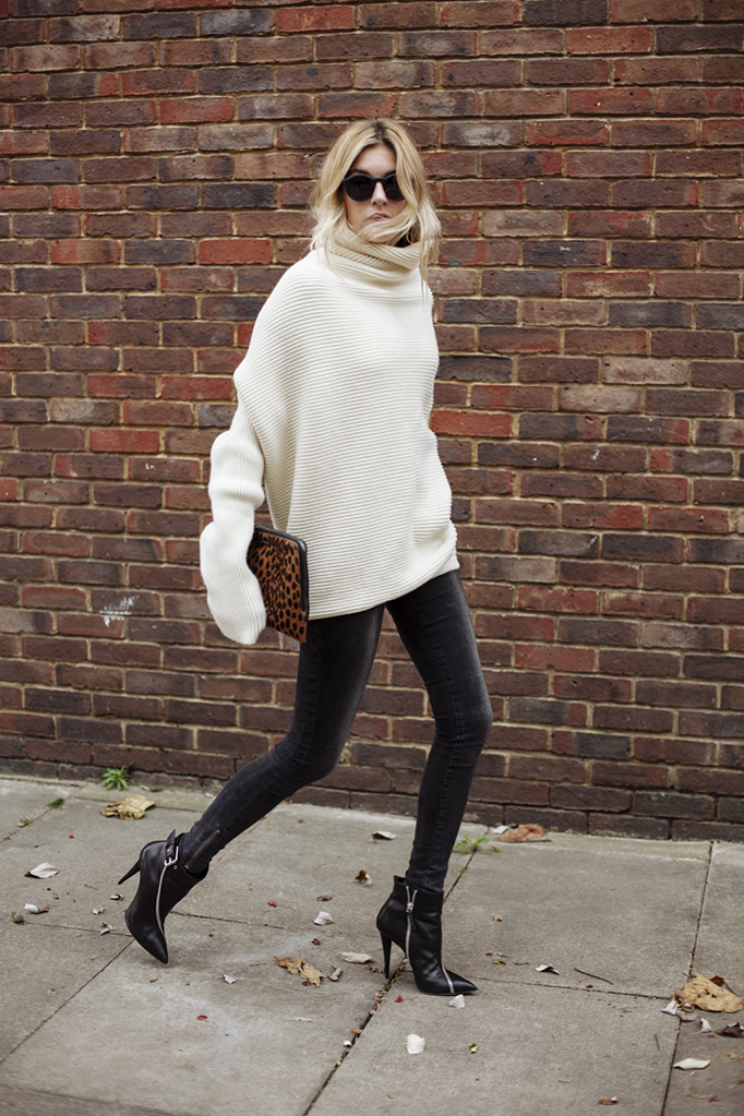 Camille Charriere is wearing black jeans from Anine Bing, boots from Giuseppe Zanotti, white knit top from Acne and the clutch is from Elizabeth & James