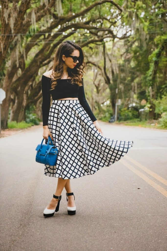 Accessorise A Black And White Outfit: Daniela Ramirez is wearing a Shoppiin midi skirt with a black Daily Look crop top and a Zinc blue handbag