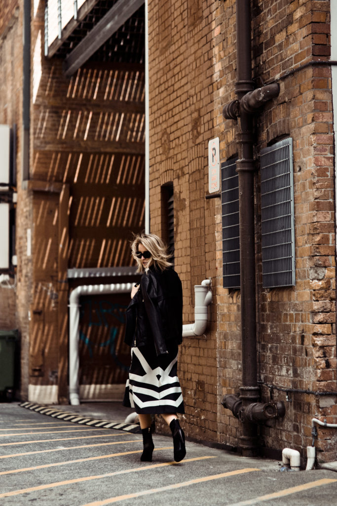 Black and White Outfit Ideas: Mandy Shadforth is wearing a black and white knee length skirt with a leather jacket all from Camille & Marc