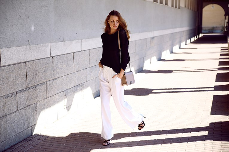 Josefin Ekstrom in a black and white outfit, black sweater, heels and flared white trousers   Sweater: Gina Tricot, Trousers: Mango, Shoes: Zara