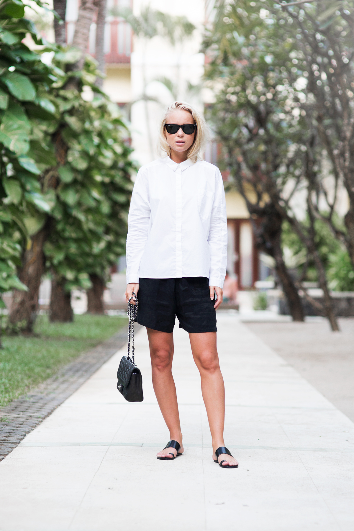 Victoria Tornegren in a white shirt, black shorts, flat sandals and a clutch bag Shirt: Monki, Shorts: Selected Femme, Shoes: ATP, Bag: Channel