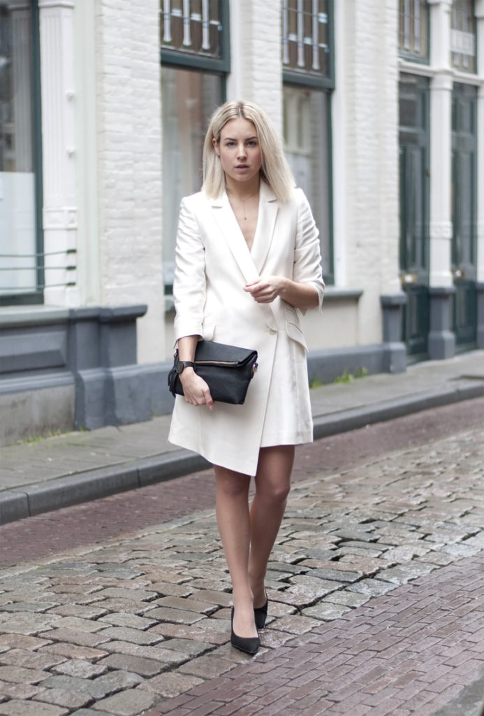 Black And White Formal Outfits: Lian Galliard is wearing a white Bastyan dress with a pair of Elizabeth Stuart heels and a Miss Guided clutch