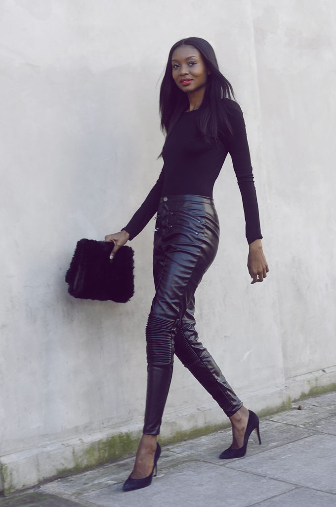 Natasha Ndlovu is in all black wearing a Miss Guided body suit and pants with an Asos clutch
