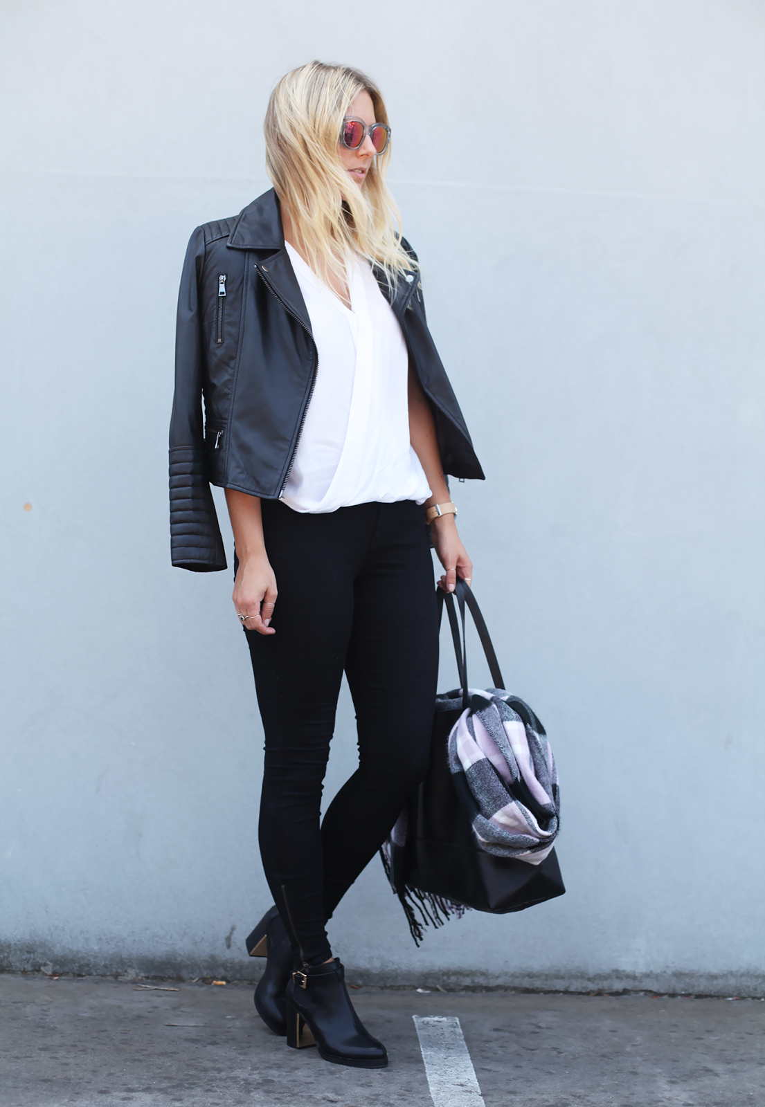 How To Wear A Black And White Outfit: Lisa Hamilton is wearing a pair of Forever New skinny jeans, a biker jacket from Jessie and black ankle boots