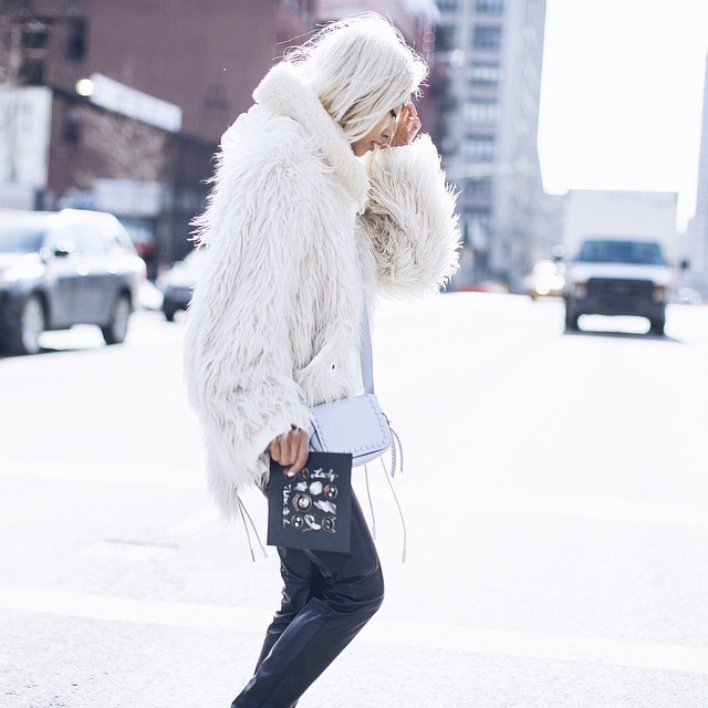 Instagram Fashion: @thehautepursuit is wearing a fluffy white coat with black trousers and a pastel side bag