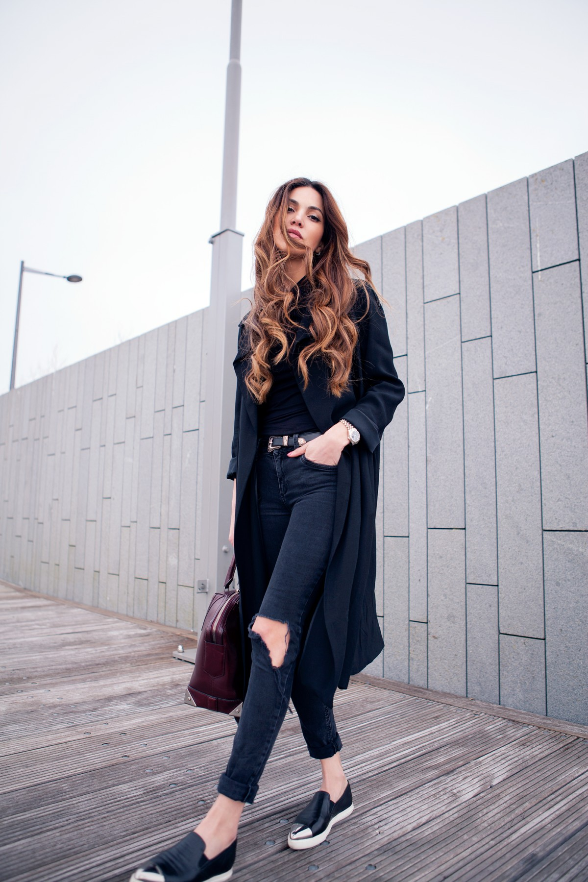Via Just The Design: Negin Mirsalehi is wearing an oversized black coat with River Island skinny jeans with a pair of black Miu Miu pumps