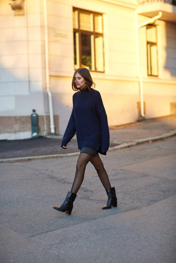Darja Barannik demonstrates just how to wear the black and blue trend, pairing a navy sweater with a black mini skirt and leather boots to create a cosy winter style which we adore.   Brands not specified.
