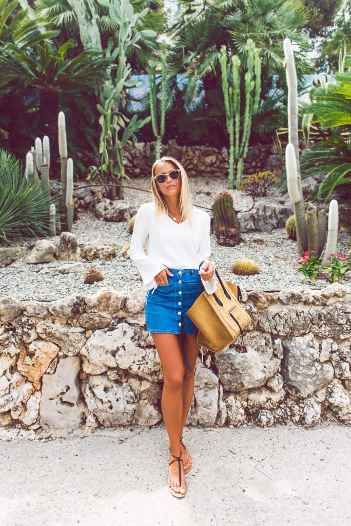 Pair your little button front denim mini skirt with a simple white bell sleeve blouse. Adorable. Via Janni Deler  Sunglasses: RayBan, Top: Chiquelle, Skirt: Gina Tricot, Bag: Céline, Sandals: Bershka