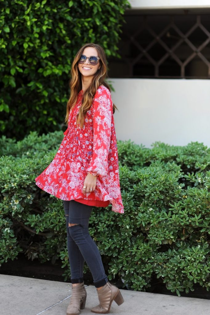 Merrick White is wearing a red floral Nordstrom dress over a pair of dark grey skinny jeans