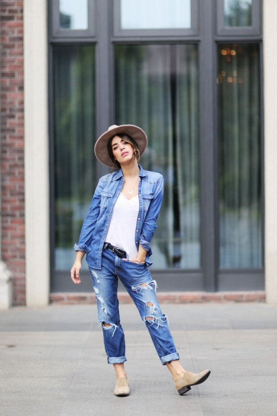 Aida Domenech wears a classic denim shirt over a plain white tee and ripped denim jeans. Denim: Pepe Jeans, Shirt and Hat: Stradivarius, Shoes: Asos, Jewellery: Maria Pascual.