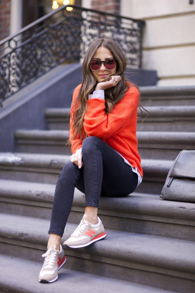 Arielle Nachami is wearing an orange Alexander Wang sweater