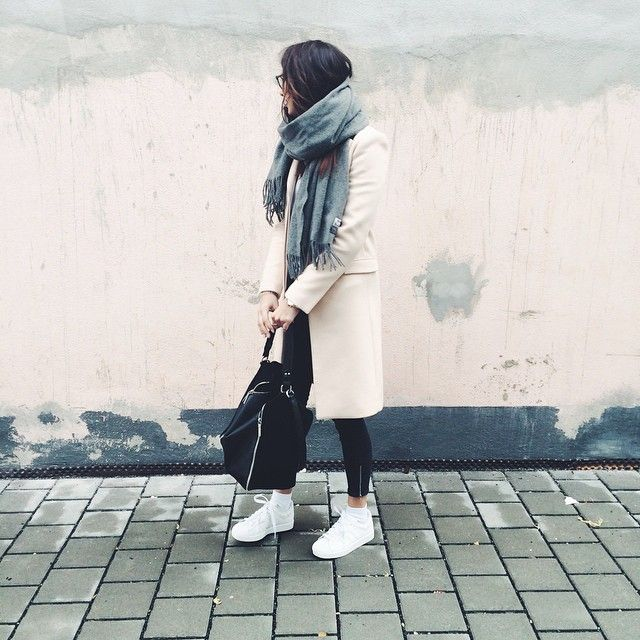 Jacqueline Isabelle is wearing a three quarter length coat, grey scarf and white sneakers