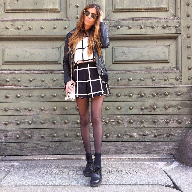Enrica Albani is wearing black and white big pane skirt and top, leather jacket and Doc Martens shoes