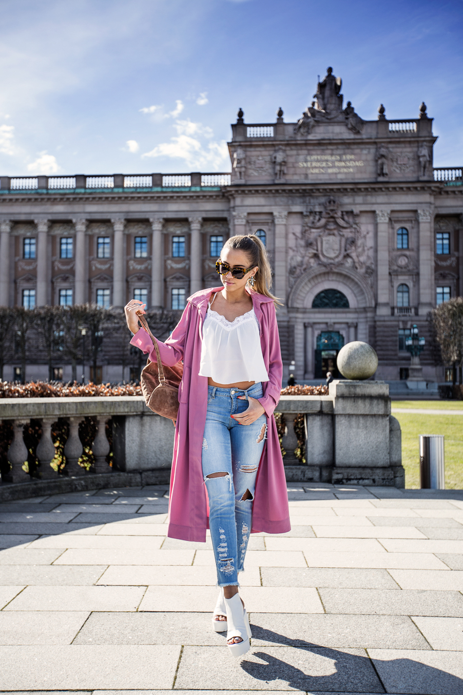 Via Just The Design: Kenza Zouiten is wearing a pink trench coat with a white NYL lace top, denim skinny jeans and white wedges