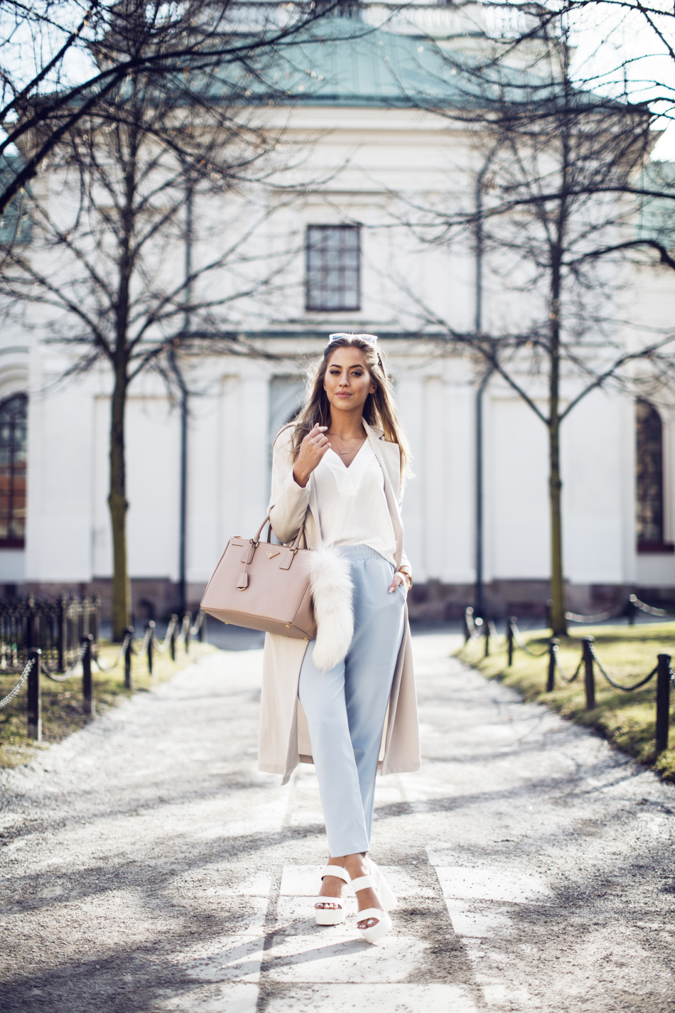 Just The Design: Kenza Zouiten is wearing a creme Ginatricot coat and blouse with baby blue high waisted trousers and white NYL heels