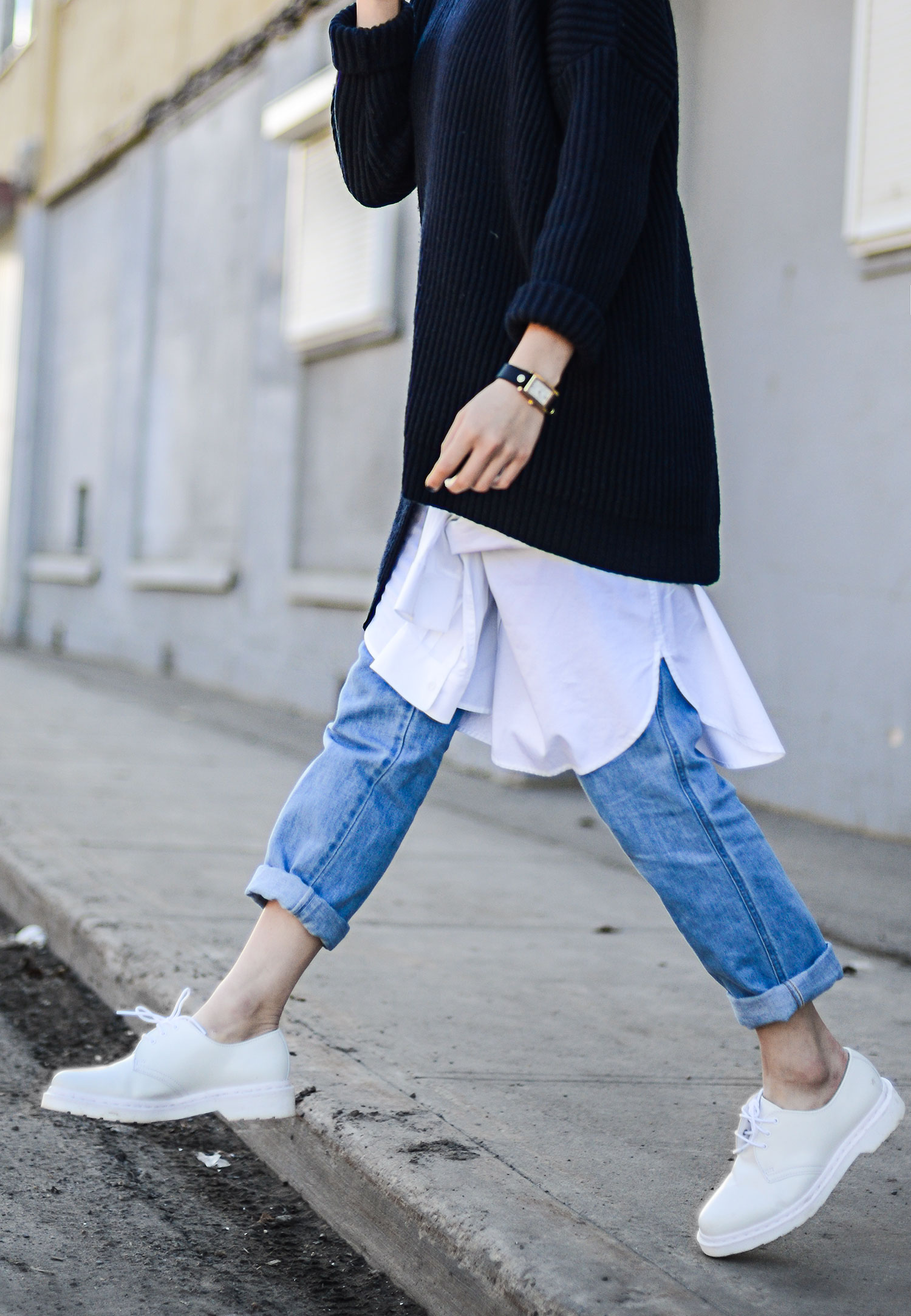 The Long Over Long Trend: Alyssa Lau is wearing a vintage knitted jumper and a white Vera Wang skirt over a pair of New Classics Studios light wash denim jeans