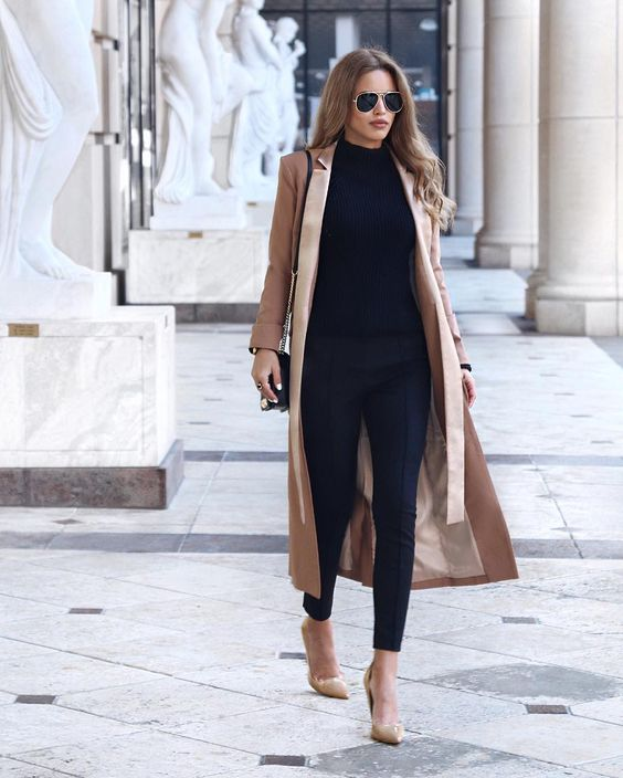 Nada Adelle wears a silky beige maxi coat with black cigarette trousers, a black turtleneck, and a pair of matching beige flats. Wear this look with shades to steal Nada's sophisticated style.  Coat: Lavish Alice, Bag: Rebecca Minkoff, Shoes: Topshop.