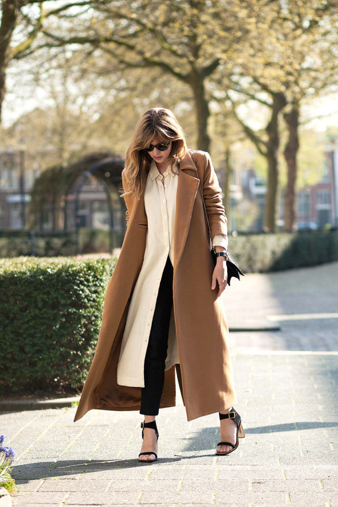 Christine R. is wearing a brown coat from Charlie May, off white shirt dress from Ganni shirt, black COS trousers, and sandals from Céline