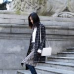 Claire Liu is wearing a chevron wrap skirt over jeans, from Self Portrait and J Brand respectively