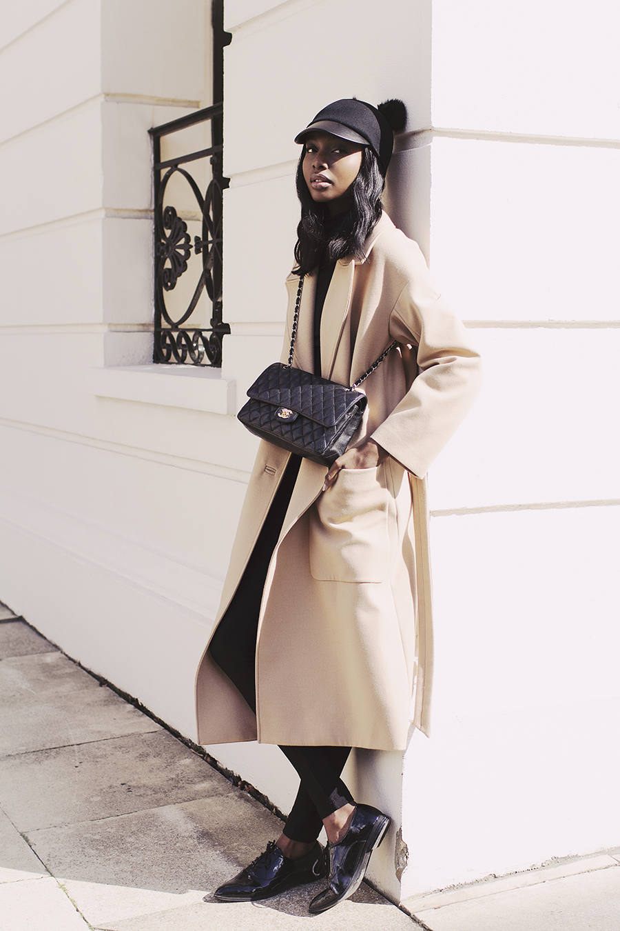 Natasha Ndlovu looks effortlessly cool as she pairs her long cream coat with skinny cigarette trousers and a black peaked cap. Coat: J.Lindeberg, Turtleneck: ASOS.