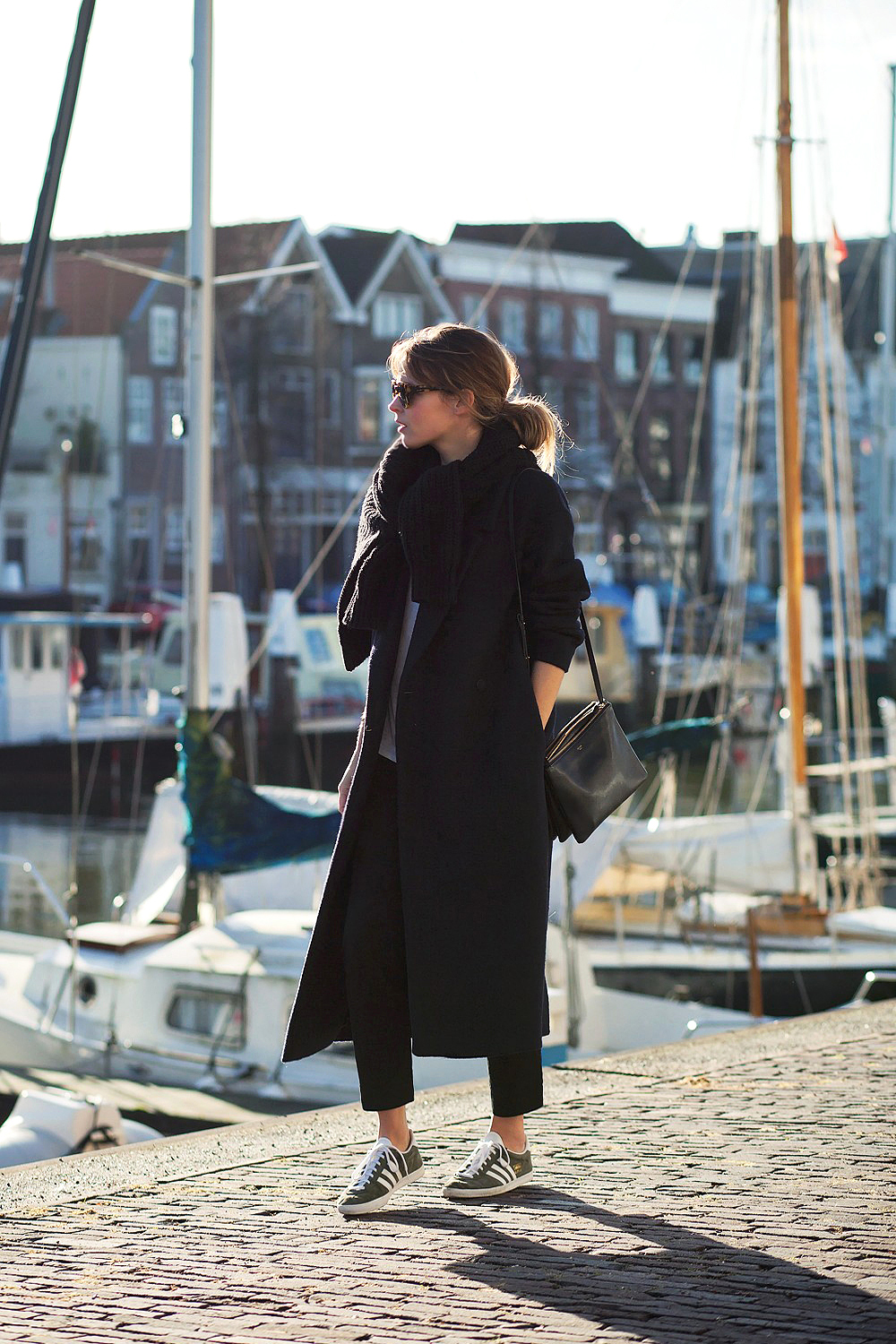 A black maxi coat is a must have for a classy winter style. Christine R. wears this oversized coat with cigarette trousers and sneakers; a casual and easy christmas look. Coat/Tee/Trousers: COS, Sweater: Ganni, Sneakers: Adidas, Bag: Céline.