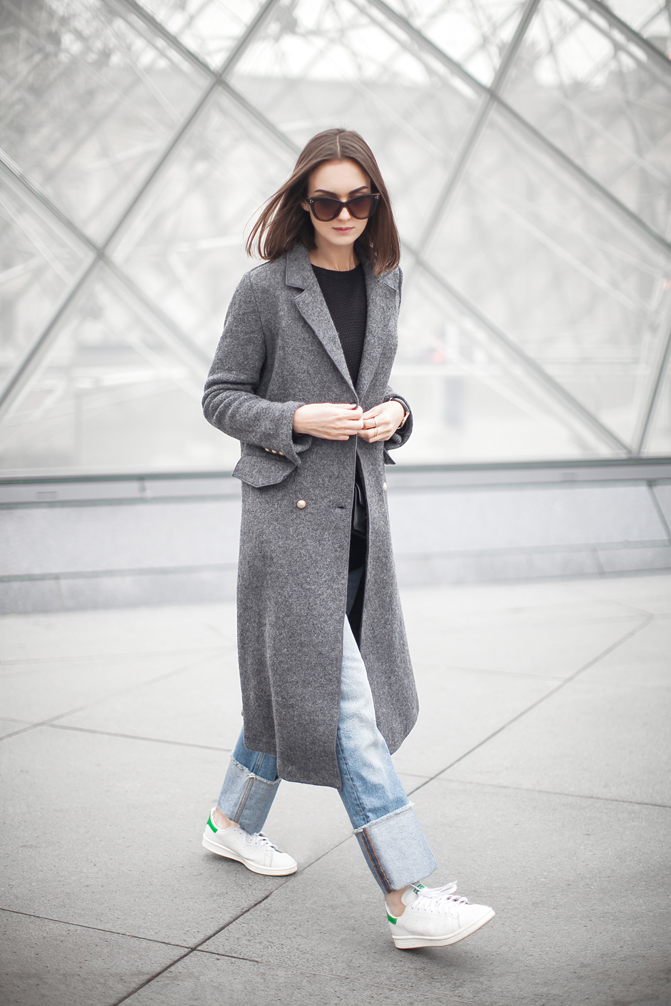 A grey maxi coat such as this will always add a touch of sophistication and glamour to your every day outfit. Nika Huk wears this Zara piece over rolled jeans and a pair of Adidas Stan Smiths. Coat: Zara, Sweater/Jeans: H&M, Shoes: Adidas, Bag: Saint Laurent.