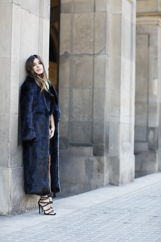 A faux fur floor length maxi coat like this one will add instant glamour to your outfit. Aida Domenech wears this dark fur with strappy black heeled sandals; an edgy and individual style. Outfit: Missguided.