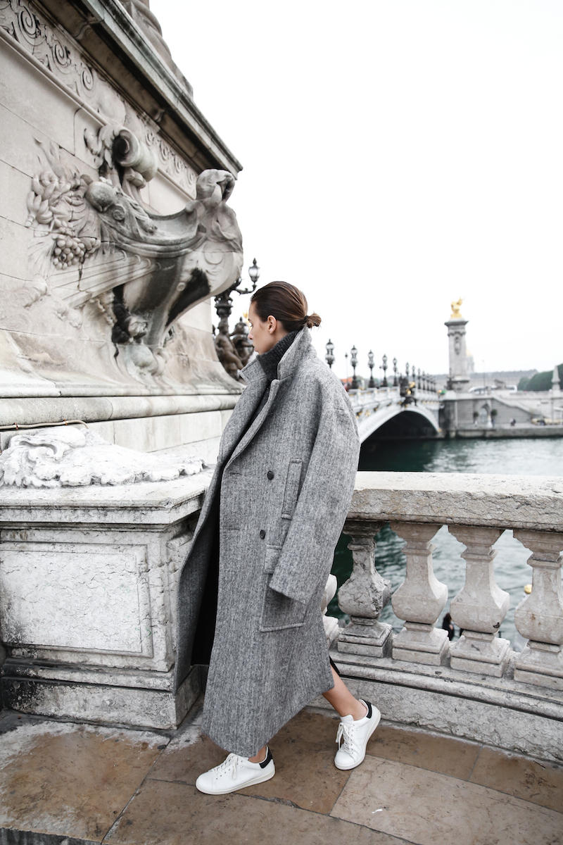 Kaitlyn Ham is rocking the oversized maxi coat trend, generating a uniquely androgynous style by wearing this broad coat with simple white sneakers. Coat/Dress: Raey, Sneakers: Isabel Marant.