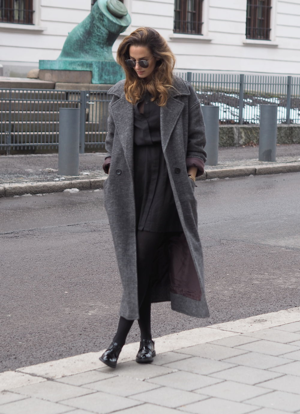 This bulky grey maxi coat goes perfectly with Benedichte's sleek and stylish monochrome outfit. In a shirt dress and patent brogues, she is rocking a more androgynous style! Jacket/Shirt Dress: Vagabond, Shoes: Zalando.