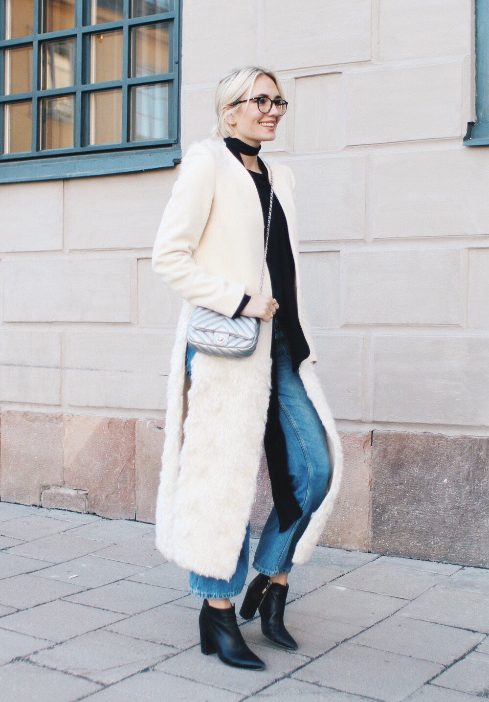 Josefin Dahlberg looks chic and stylish in this elegant faux fur maxi coat, paired with Chelsea boots and flared jeans. Throw in a skinny scarf to add edge and an extra kick to your outfit! Brands not specified.