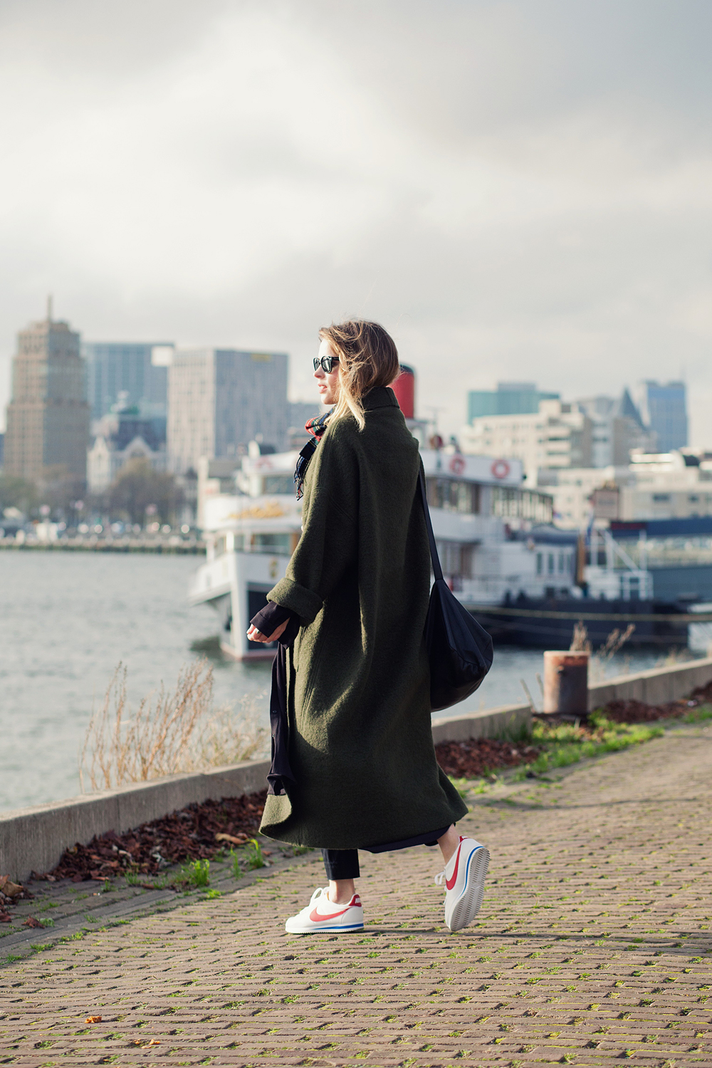 Wear the maxi coat trend like Christine R with a pair of cute sneakers, cigarette trousers, and a tartan scarf to accessorise. Coat: Designed by Christine, Trousers/Bag: COS, Sneakers: Nike.