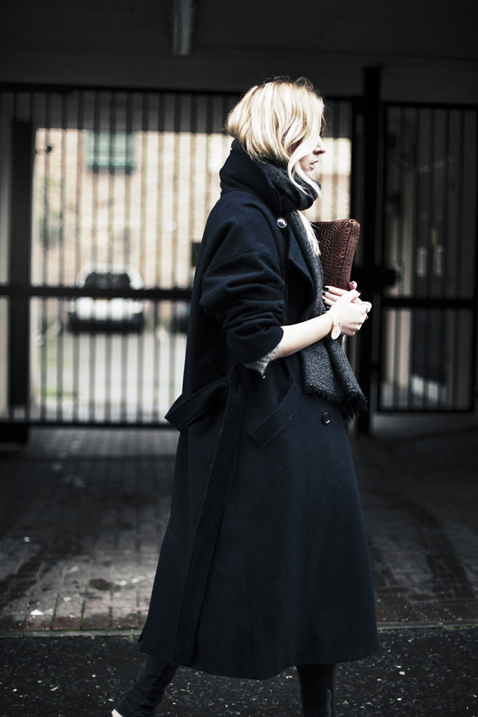 Camille Charriere is wearing a black maxi coat from Ganni