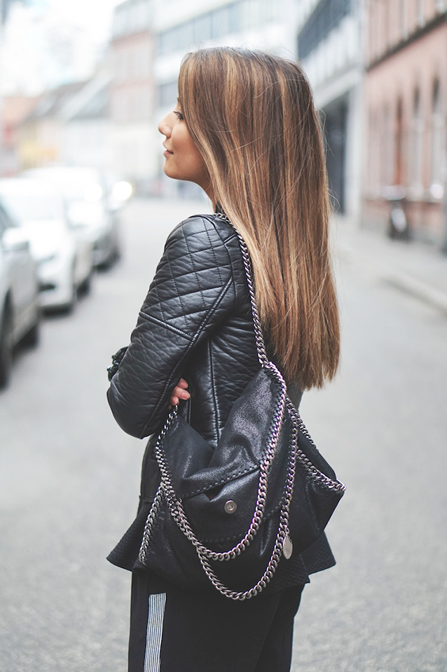 Michelle Nielsen is wearing a leather biker jacket with a black handbag