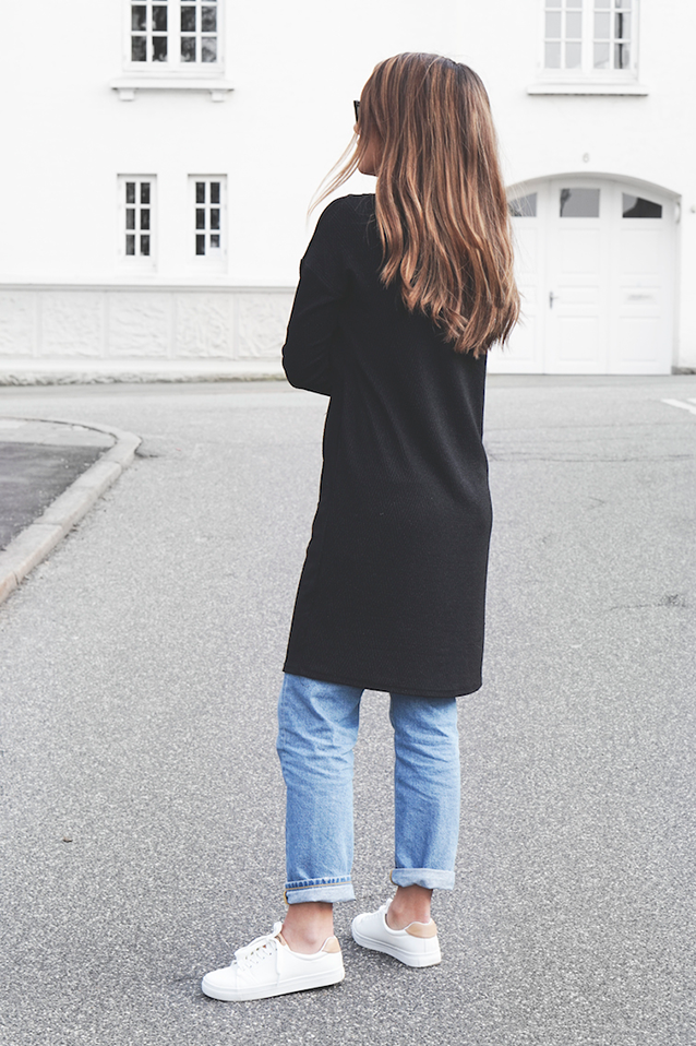 The Long Over Long Trend: Michelle Nielsen is wearing a black trench over a pair of light wash denim mom jeans