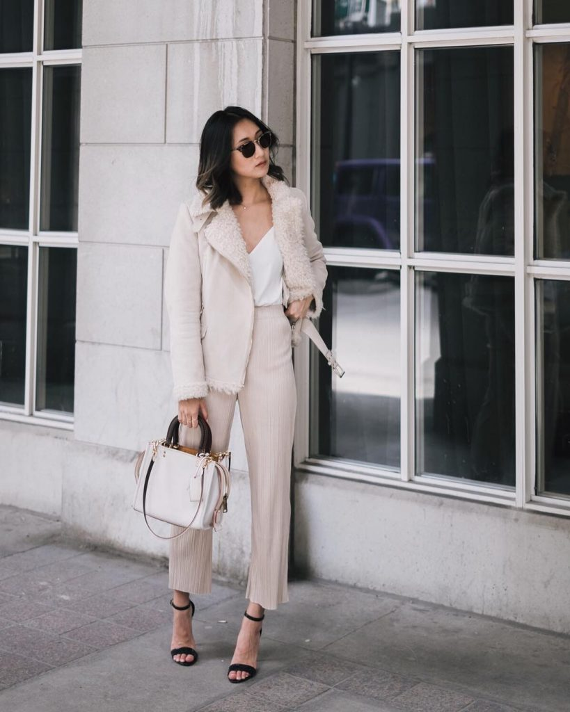 Tina Hu's neutral outfit consists of a faux fur trimmed suede jacket, a white V neck cami, and a pair of gorgeous nude trousers, with a high waist to accentuate the figure.   Bag: Coach.
