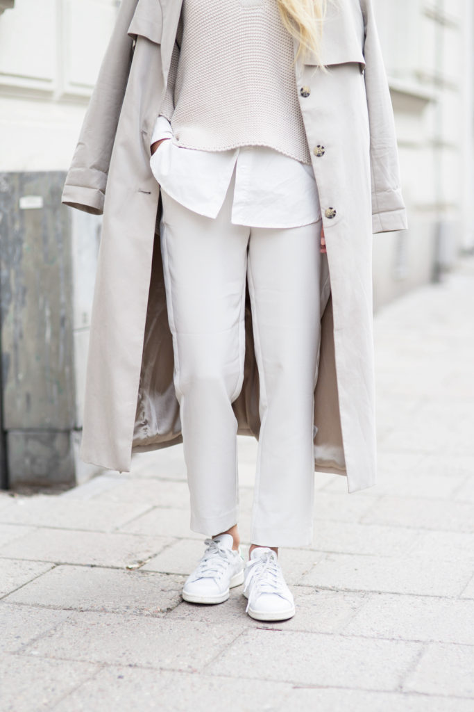 Victoria Tornegren is wearing a beige sweater and trousers from Gina Tricot, draped trench coat from Monki and the sneakers are from Adidas
