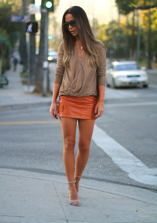 Johanna Olsson looks ultra cute in this orange leather mini skirt, worn with a simple beige V neck top and heeled sandals. This summery look is perfect for hitting the town day or night! Brands Not Specified.