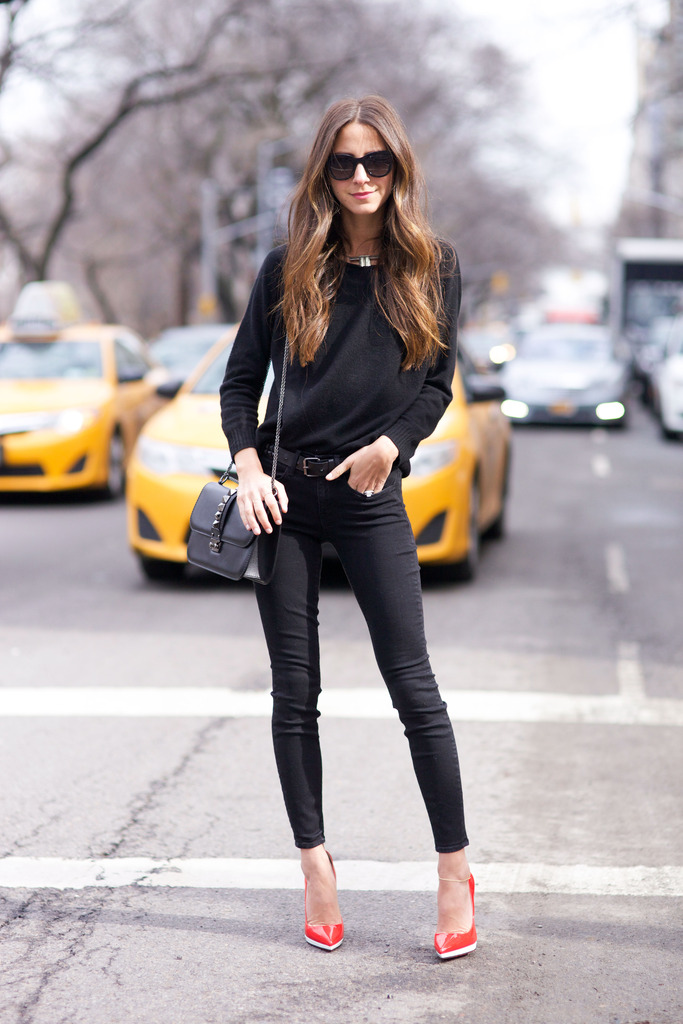 Arielle Nachami is wearing black jeans from AYR, red shoes from Christian Louboutin, black sweater from Inhabit, matching bag from and the sunglasses are from Anine Bing