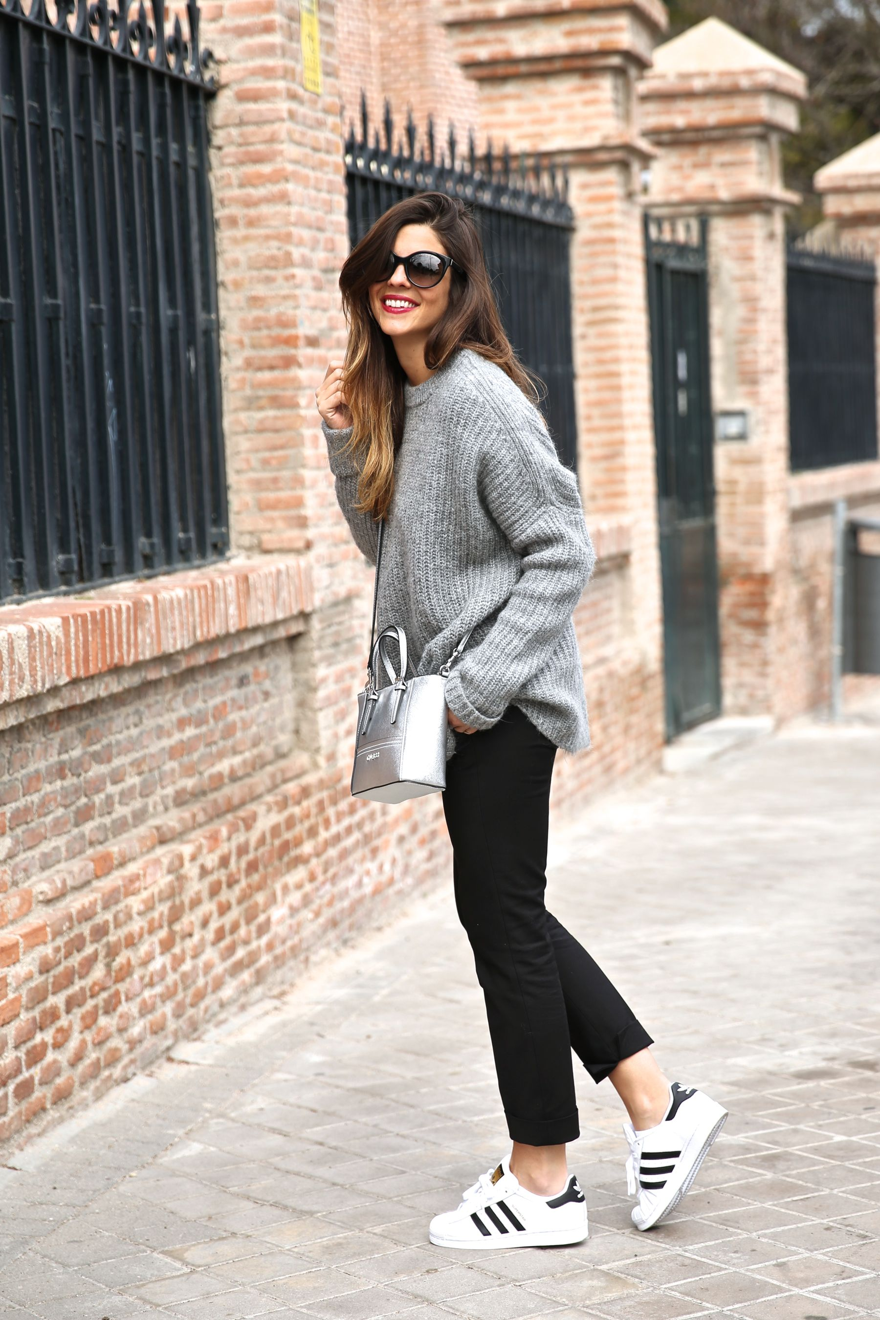 Natalia Cabezas is wearing a grey knit sweater and black trousers from Zara, sneakers from Adidas, sunglasses from Prada and the bag is from Guess