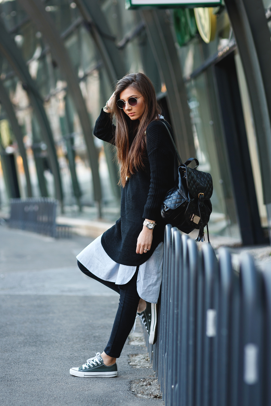 Larisa Costea is wearing a black long sweater, tunic and ripped jeans all from Sheinside, sneakers from Converse and the backpack is from Jadu