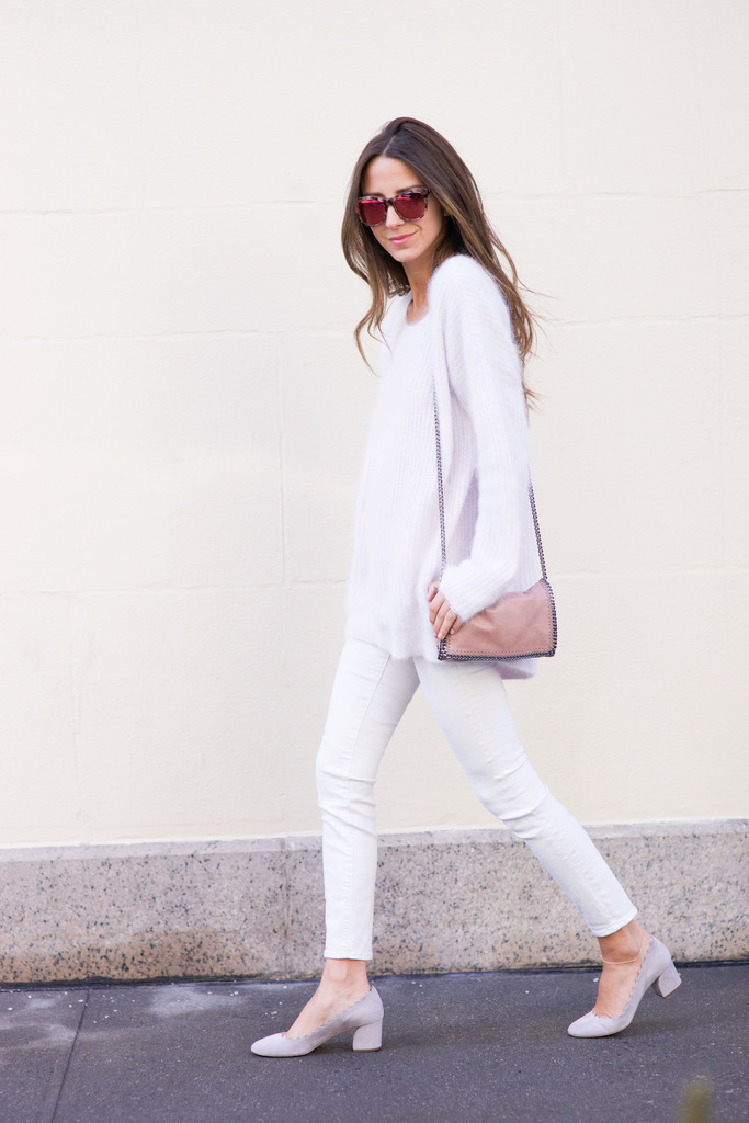 Arielle Nachami is wearing white jeans from AG, blush shoes from Chloe, fluffy sweater from Intermix, sunglasses from Wildfox, and the bag is from Stella McCartney