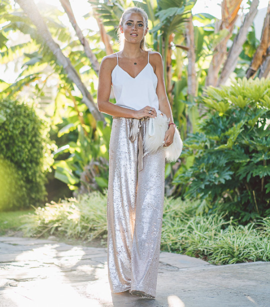 Is there anything more glam than these sequined wide leg trousers? We don't think so! Janni Deler looks utterly gorgeous in these striking trousers, worn stylishly with a simple white vest. Top: Ivy Revel, Trousers: Malina, Bag: River Island.